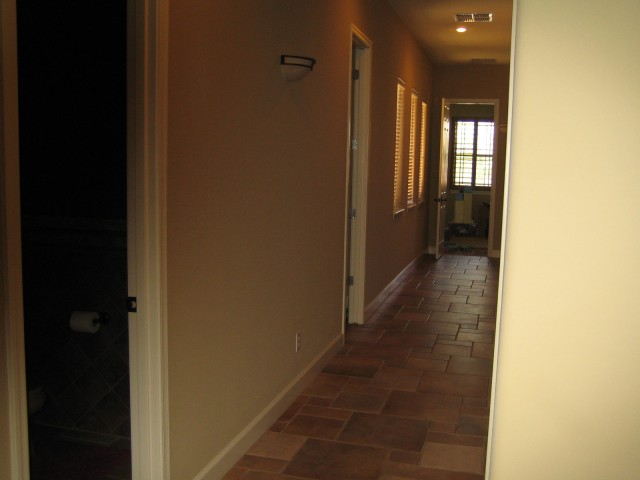Looking down the hall from kitchen Powder, then kids' bath. Playroom at end of hall. Kid's bedrooms on right.